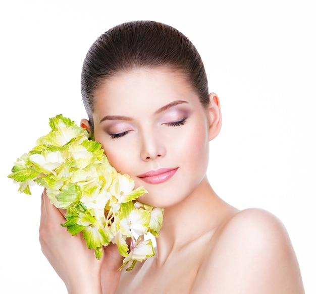 Portret pięknej młodej kobiety z zielonym kwiatem - na białym tle