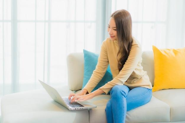Portret pięknej młodej kobiety za pomocą laptopa na kanapie w salonie