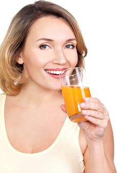 Portret pięknej młodej kobiety ze szklanką soku pomarańczowego na białym tle.