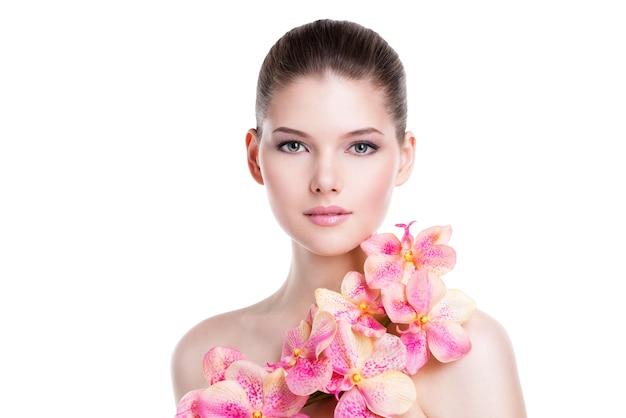 Portret pięknej młodej kobiety ze zdrową skórą i różowe kwiaty na ciele - na białym tle
