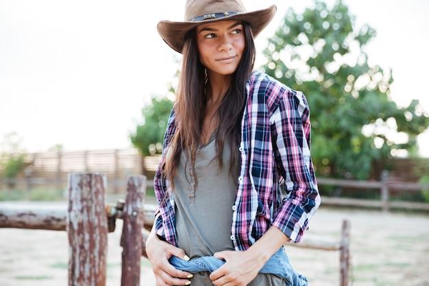 Portret pięknej młodej kowbojki w kapeluszu stojącej na ranczo