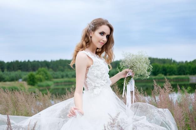 Portret pięknej młodej ładnej narzeczonej w białej stylowej sukni ślubnej z bukietem ślubnym w dłoni