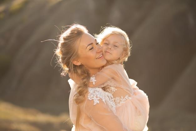 Portret pięknej młodej mamy trzyma w ramionach ukochaną córkę. rodzicielska miłość, mała księżniczko