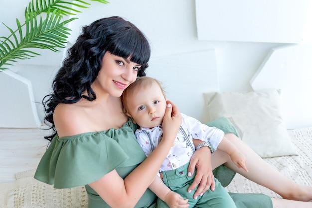 Portret pięknej młodej matki przytulanie dziecka w jasnym pokoju w zielone ubrania, matka i syn, dzień matki