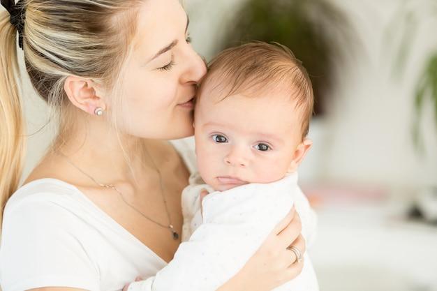 Portret pięknej młodej matki trzymającej dziecko na rękach