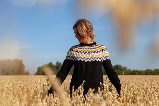 Portret pięknej młodej modelki w ciepłych ubraniach, ciesz się dniem, na polu w słoneczny jesienny dzień. pojęcie jedności kobiety i natury, spokojnego nastroju, życia przyjaznego środowisku
