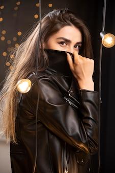 Portret pięknej młodej modelki w czarnej skórzanej kurtce pozowanie w pobliżu lamp.
