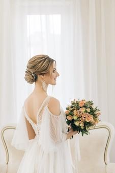 Portret pięknej młodej narzeczonej w jasnym pokoju w romantycznej atmosferze. zbliżenie: makijaż ślubny i fryzurę