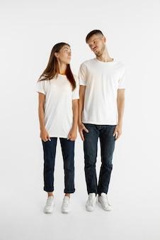 Portret pięknej młodej pary na białym tle na tle białego studia. wyraz twarzy, ludzkie emocje, koncepcja reklamy. mężczyzna i kobieta stojąc i patrząc na siebie.