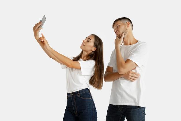 Portret pięknej młodej pary na białym tle. wyraz twarzy, ludzkie emocje. kobieta robi selfie, mężczyzna się nudzi, nie chce.