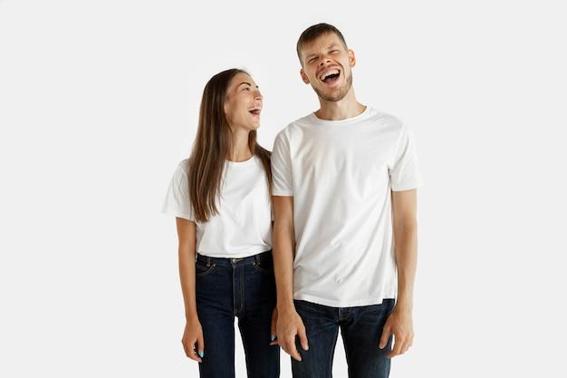 Portret pięknej młodej pary na białym tle. wyraz twarzy, ludzkie emocje. mężczyzna i kobieta stojąc, patrząc na siebie i uśmiechając się.