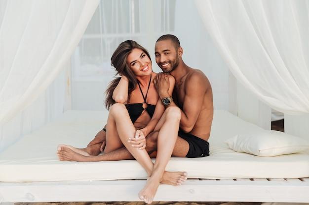 Portret pięknej młodej pary razem siedzi na białym łóżku