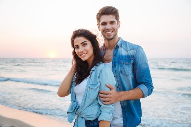 Portret pięknej młodej pary stojącej i uśmiechającej się na plaży