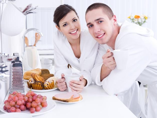 Portret pięknej młodej pary uśmiechający się jedząc śniadanie w kuchni