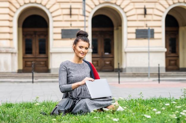 Portret pięknej młodej studentki uśmiechający się studiując z laptopem na trawie w pobliżu