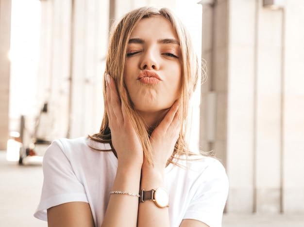 Portret pięknej modelki blond ubrani w letnie ubrania hipster. . sprawia, że twarz kaczki