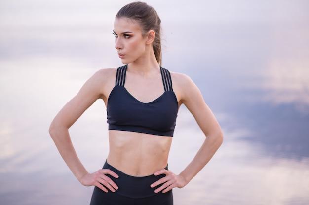 Portret pięknej modelki fitness na tle morza o zachodzie słońca