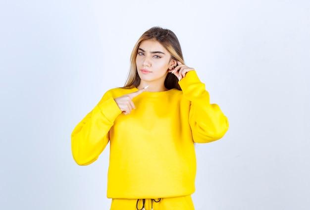 Portret pięknej modelki stojącej i pozującej w żółtej koszulce