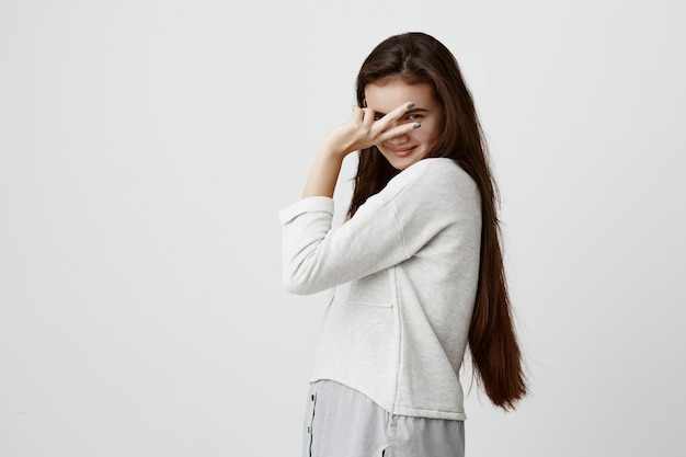 Portret pięknej modelki z ciemnymi długimi włosami, nosi ubrania codzienne, czuje się szczęśliwy i zrelaksowany w pomieszczeniu, pokazując znak v. ładna kobieta uśmiecha się wesoło, gestykuluje, wyraża pozytywne emocje
