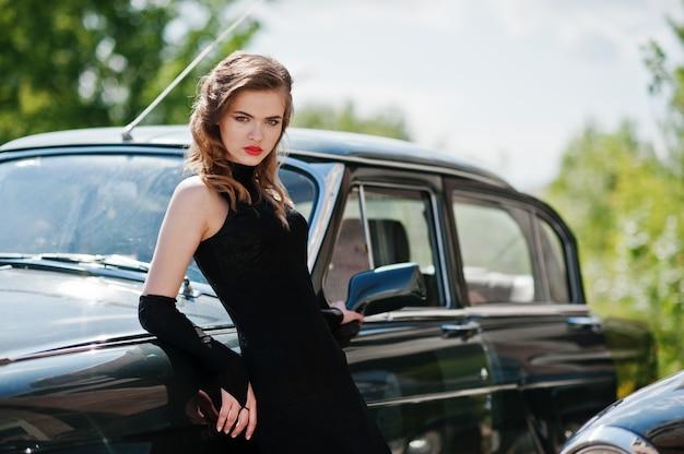 Portret pięknej modelki z jasnym makijażem w stylu retro, oparł się na zabytkowym samochodzie