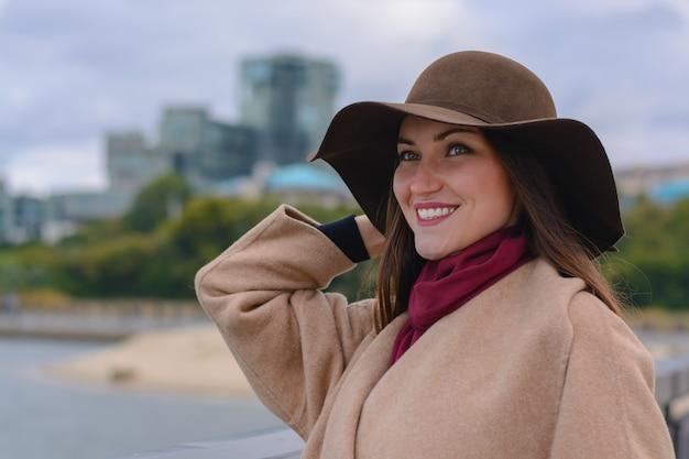 Portret pięknej modnej młodej kobiety w kapeluszu i płaszczu na brzegu rzeki w mieście.