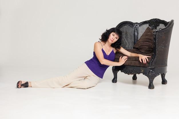 Portret pięknej, modnej modelki siedzącej na krześle w stylu art nouveau. biznes, elegancka bizneswoman. wnętrze, meble.