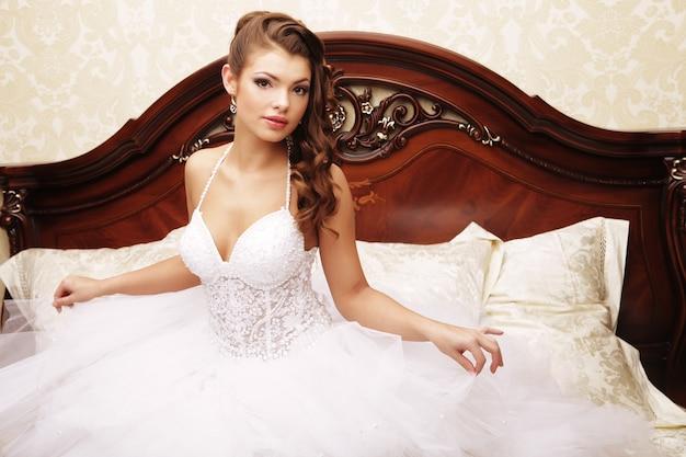 Portret pięknej narzeczonej na łóżku w dzień ślubu
