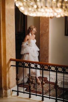 Portret pięknej narzeczonej schodzącej po schodach w holu.