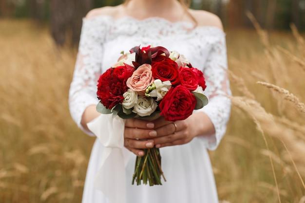 Portret pięknej narzeczonej trzyma bukiet ślubny z czerwonych róż na zewnątrz w słoneczny dzień. młoda dziewczyna w białej sukni z świątecznym jasny bukiet o charakterze. dzień ślubu . bukiet ślubny