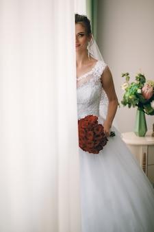 Portret pięknej narzeczonej w białej jedwabnej szlafroku z kręconymi fryzury i długi welon stojący w pobliżu okna w sypialni