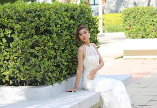 Portret pięknej narzeczonej w białej sukni ślubnej z długim pełnym spódnicy siedzi w parku. widok z boku z miejsca na kopię.