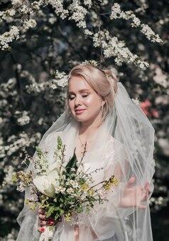 Portret pięknej narzeczonej z kwiatami w ogrodzie wiosną. suknia ślubna.