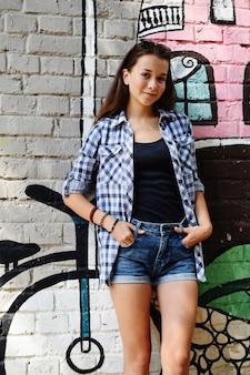 Portret pięknej nastolatki ubrany był w kraciastą koszulę i jeansowe szorty, przy ścianie z jakimś elementem graffiti.