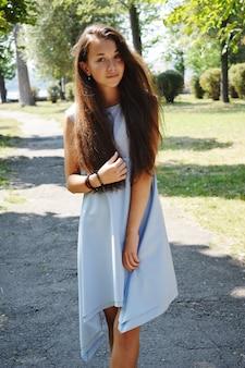 Portret pięknej nastolatki w niebieskiej bluzce, na tle zieleni parku latem grać z jej włosów.