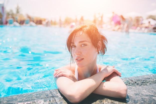 Portret pięknej opalonej kobiety w biały strój kąpielowy relaks w basenie spa. gorący letni dzień i jasne słoneczne światło.