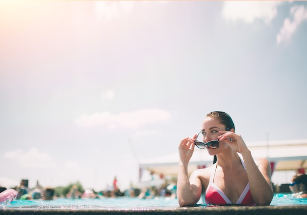 Portret pięknej opalonej kobiety w białym stroju kąpielowym relaks w basenie spa. gorący letni dzień i jasne słoneczne światło