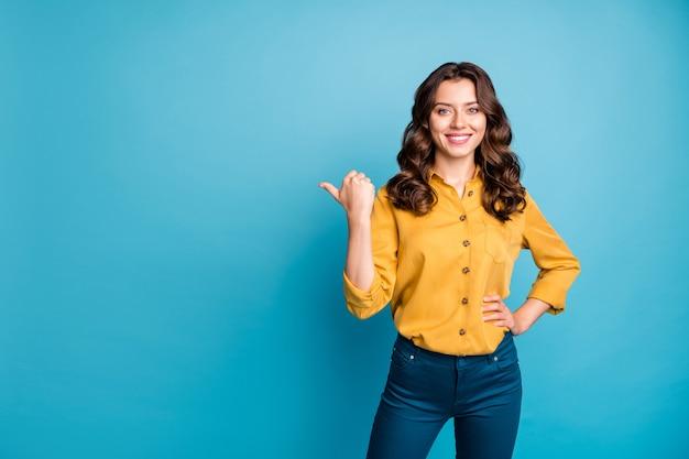 Portret pięknej pani menadżer wskazujący kciuk pusty obszar doradzający nowy produkt niska cena nosić żółte spodnie koszuli.