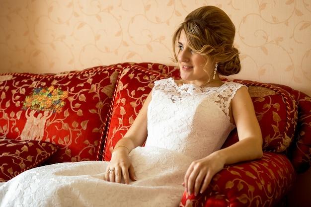 Portret pięknej panny młodej relaksującej się na kanapie w luksusowym pokoju hotelowym