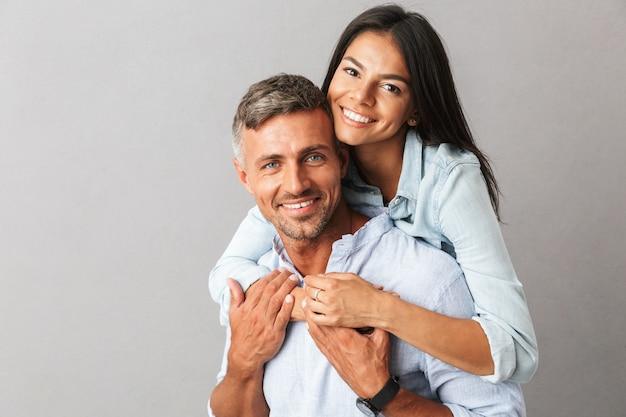 Portret pięknej pary mężczyzny i kobiety w podstawowej odzieży, uśmiechając się i przytulając razem, odizolowane na szaro