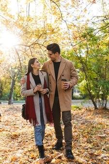 Portret pięknej pary pijącej kawę na wynos z papierowych kubków i patrzących na siebie podczas spaceru w jesiennym parku