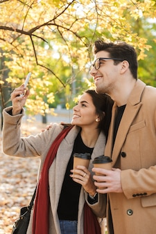 Portret pięknej pary pijącej kawę na wynos z papierowych kubków i robienia zdjęć selfie na telefonie komórkowym podczas spaceru w jesiennym parku