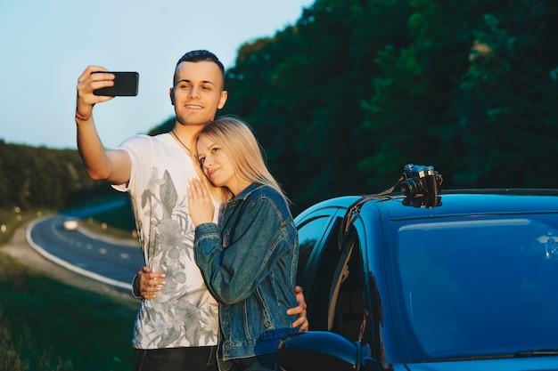 Portret pięknej pary przy selfie obejmując się w pobliżu ich samochodu, odpoczywając przy drodze podczas podróży samochodem.