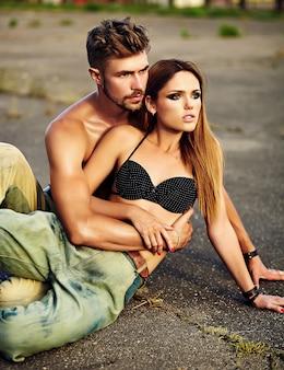 Portret pięknej pary. seksowny stylowy blond młoda kobieta model z jasnym makijażem z idealną opaloną skórą i przystojny umięśniony mężczyzna w dżinsach na zewnątrz na tle asfaltu