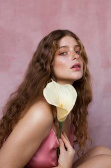 Portret pięknej piegowatej kobiety trzymającej kwiat