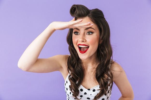 Portret Pięknej Pin-up Girl Noszącej Jasny Makijaż, Stojącej Na Białym Tle Nad Fioletową ścianą, Krzyczącej Głośno Premium Zdjęcia