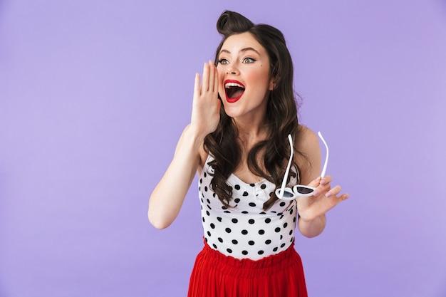 Portret pięknej pin-up girl noszącej jasny makijaż, stojącej na białym tle nad fioletową ścianą, krzyczącej głośno