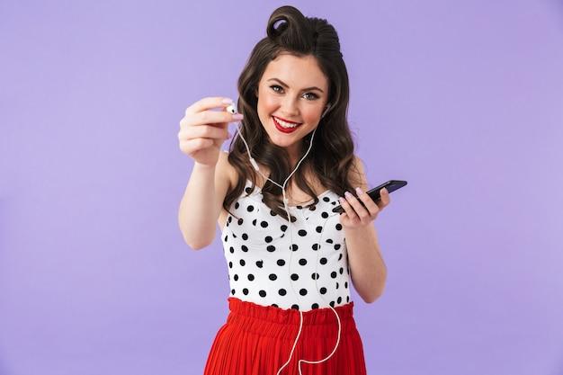 Portret pięknej pin-up girl noszącej jasny makijaż, stojącej na białym tle nad fioletową ścianą, słuchającej muzyki przez słuchawki i telefon komórkowy
