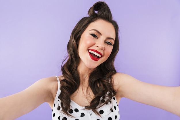 Portret pięknej pin-up girl noszącej jasny makijaż stojący na białym tle nad fioletową ścianą, biorąc selfie