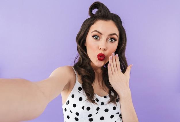 Portret Pięknej Pin-up Girl Noszącej Jasny Makijaż Stojący Na Białym Tle Nad Fioletową ścianą, Biorąc Selfie Premium Zdjęcia