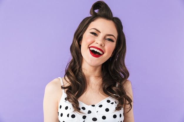 Portret pięknej pin-up girl noszącej jasny makijaż stojący na białym tle nad fioletową ścianą, dopingująca, świętująca